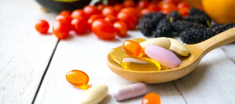 Vitamin B12 und vegane Ernährung. Nahrungsergänzung. Pillen und Kapseln auf einem Holzlöffel.