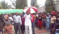 Obaisi Ovie Omo-Agege (centre with umbrella) besieged by women loyalist during his visit to his hometown, Orogun