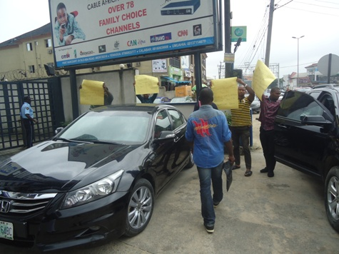 NLNG Spokesman Tony Okonedo blocked by the protesters with posters as he leaves the premises of the radio station