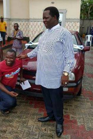 Chief Ominimini Obiuwevbi presenting a Volkswagen Golf GT automatic vehicle saloon car to  Mr. Itedjere Emoefe, a physically challenged person who also hailed from Agbarha-Otor
