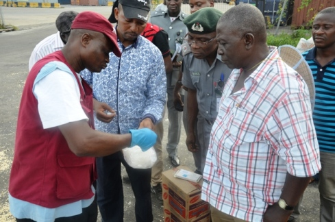 NDLEA official tests the drug while the suspect  (Right) John Vincent Arinze and other      officers watch closely