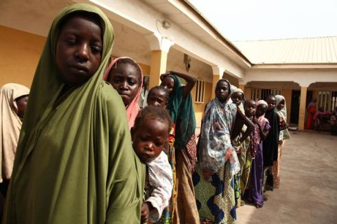 ABOVE PHOTO: Girls rescued by Nigerian soldiers from Islamist militants Boko Haram at Sambisa Forest line up to collect donated clothes at the Malkohi refugee camp in YolaGirls rescued by Nigerian soldiers from Boko Haram