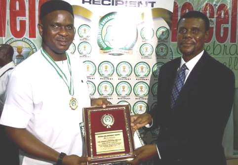 Hon Emmanuel Egbabor receiving the award from Bayo Ojo at the event