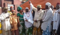 Joseph Omene (3rd from right) holds up the hand of Osu Ru Urhobo IV. Omene points to the Certificate of recognition which he issued to Osu Ru Urhobo IV.