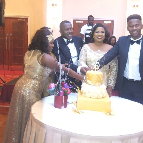 Cyril Ogue and his wife cutting the birthday cake