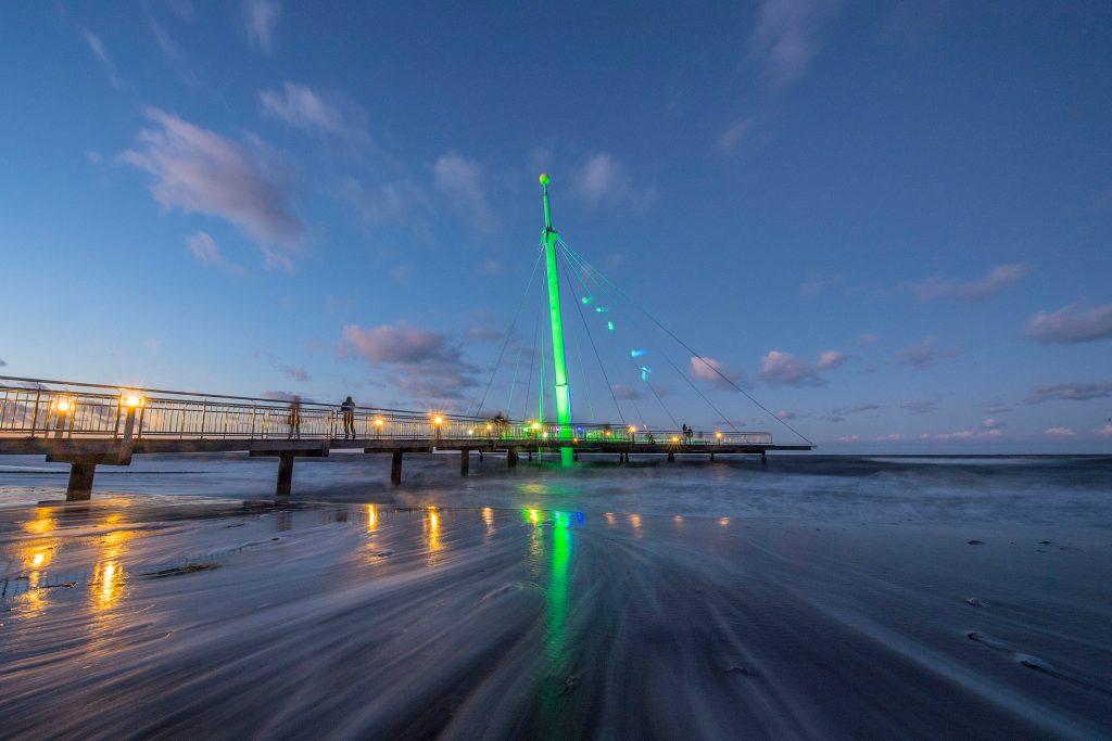 """Die """"Hohwachter Flunder"""" im Lichtermeer: Mit ihrem schon von weitem sichtbaren, 24 Meter hohen Stahlpylon ist die Seebrücke das Wahrzeichen des Ostseeheilbads Hohwacht."""