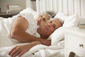 senior man looking concerned in bed with wife