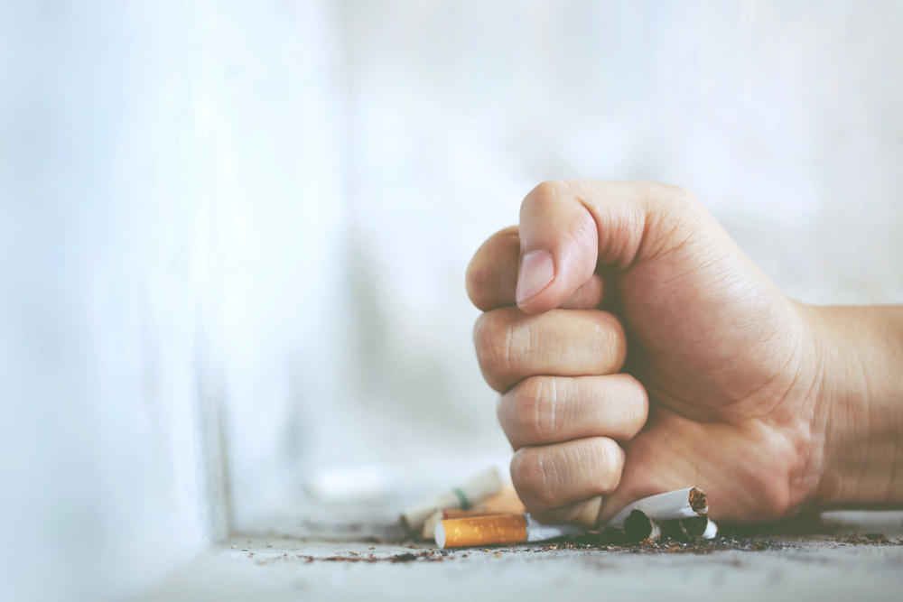 man crushing cigarette with fist