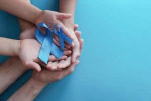 2 people's hands holding prostate cancer awareness ribbons. genetic risk concept
