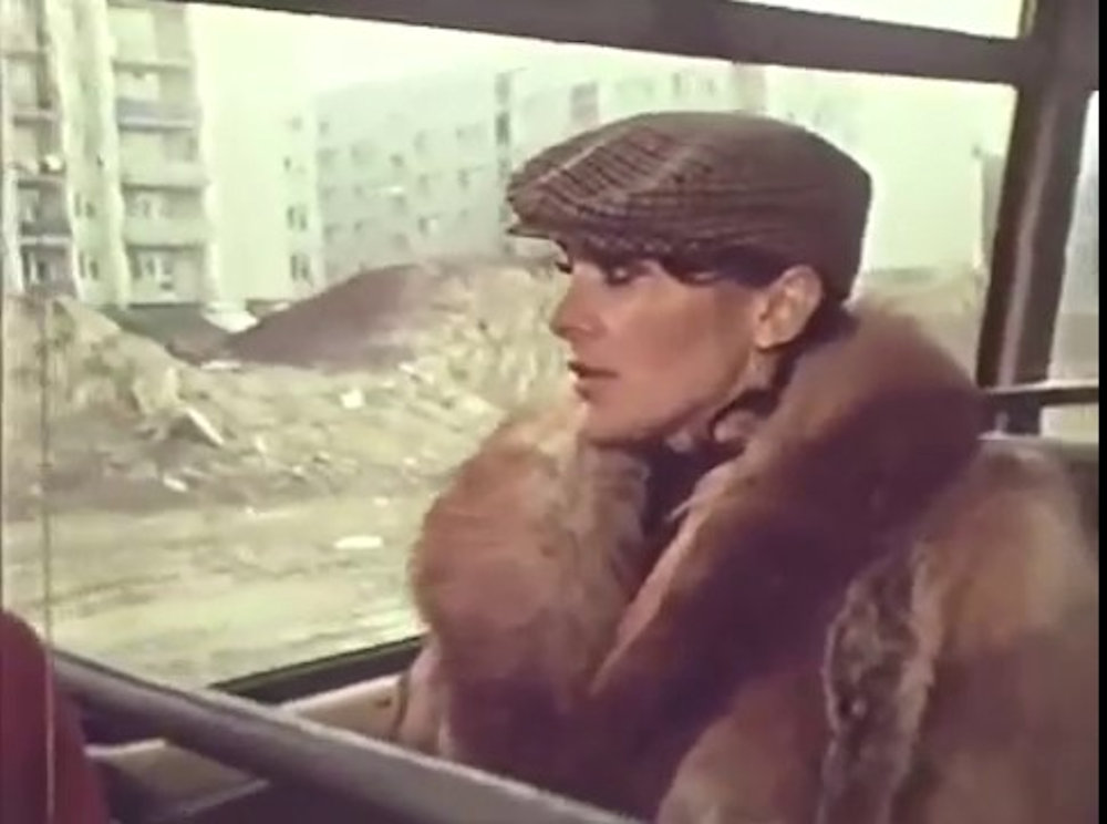 Śpiewająca pastorałkę Irena Jarocka jedzie ogórkiem. Za oknami ulica Puszczyka. Kadr z teledysku