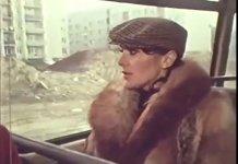 """Śpiewająca pastorałkę Irena Jarocka jedzie ogórkiem. Za oknami ulica Puszczyka. Kadr z teledysku """"Kolęda nowoprojektowana"""" (1977)."""