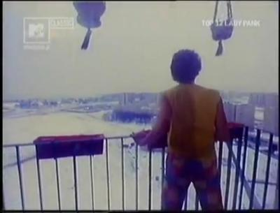 """- Gdzie spojrzę dookoła dżungla - śpiewa Lady Pank w """"Fabryce małp"""". Spogląda więc z balkonu, a dżunglą jest tu osiedle Na Skraju: lasek imieliński i widoczna po lewej, acz nieco rozmazana wielka baza budowlana przy Rosoła. Kadr z MTV Classic."""