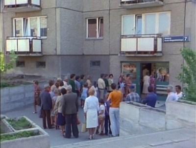 """Kolejka do filmowego mięsnego na Szolc-Rogozińskiego 7. To ten sklep, który w """"Alternatywach"""" był miejscem testu robota kolejkowego. Kadr z serialu """"Zmiennicy""""."""