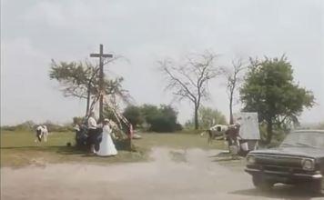 """Dziś za krzyżem jest już kościół na szczycie Skarpy u wylotu Imbirowej, ale sam krzyż stoi jak stał. Studnia zresztą też. Kadr z filmu """"Piłkarski poker""""."""