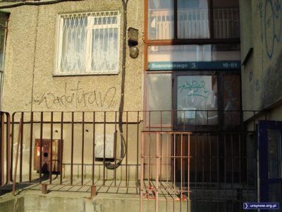 Tylne wejście do budynku Sosnowskiego 3. Wiązki kabli to zewnętrzna instalacja pionierskiej telewizji kablowej. Jest też charakterystyczny szklany trójkącik z podświetlanym numerem domu. Zdjęcie: Marcin Grzanek.