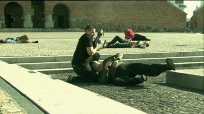 """Trup rzeczywiście pada gęsto, ale bandyci wciąż walczą z policjantami. A w tle, pod arkadami kościoła, starcie spokojnie obserwuje postronny widz. Kadr z serialu """"Pitbull"""", odc. 16."""