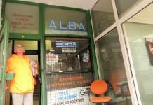 Nad wejściem do pawilonu przy Dembowskiego 8 stary szyld ALBA. Mistrz z serwisu dorabiania kluczy (na zdjęciu) tłumaczy, że chodzi o istniejącą tu 30 lat temu pralnię samoobsługową połączoną z kawiarnią dla czekających na koniec prania. Fot. Maciej Mazur.