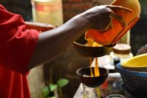 wanita jawa pada foto ini sedang membuat jamu beras kencur