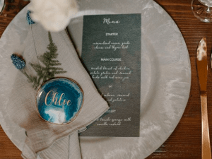 Navy menu with gold shimmer finish alongside agate slice placecard