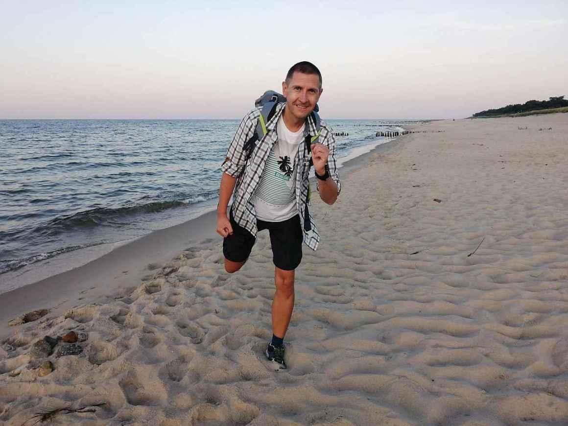 Urzędnik biega z plecakiem, biegnie wieczorem po plaży