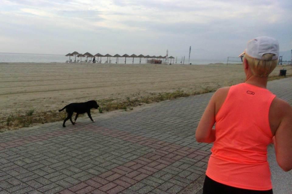 kobieta biegnie z psem przybłędą wzdłuż plaży greckie wakacje