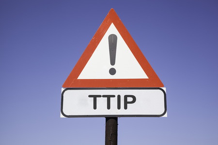 ttip: White road warning triangle with black exclamation point and red frame on a wooden mast in front of a blue sky. A second rectangular sign warns in english about TTIP