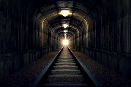 underground tunnels: A railroad tunnel with a light at the end.  Stock Photo