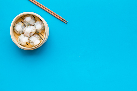 chinese food set with dim sum sticks on blue background top view copy space