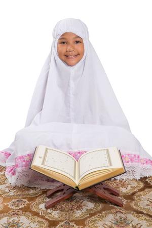 Ecco perché la ragazza dell'hijab non c'entra con le proteste. Young Asian Muslim Girl Reading Al Quran On A Prayer Mat Over White Background Stock Photo Picture And Royalty Free Image Image 27043344