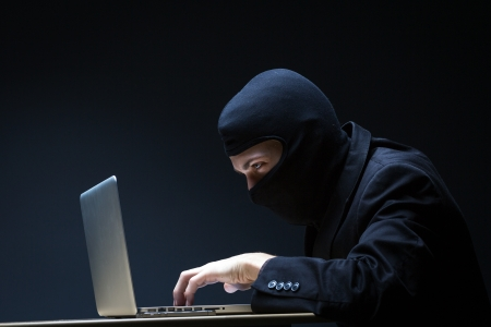 ninja: Computer hacker in a balaclava working in the darkness stealing data and personal identity information off a laptop computer Stock Photo
