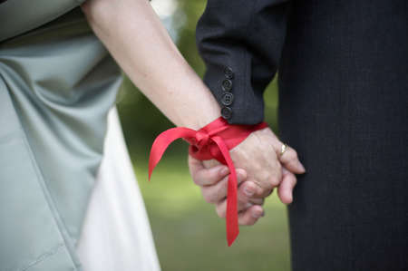 Hands tied with ribbon at wedding hand fasting ceremony Stock Photo - 3337510