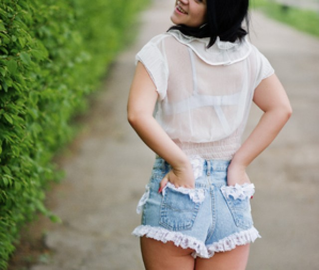 Back Of Sexy Brunette Girl On Womens Jeans Shorts And White Blouse Against Green Spring Bushes