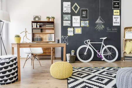 Shot of a home office with a desk, pouffs, a bike and a chalkboard wall Stock Photo - 63274511
