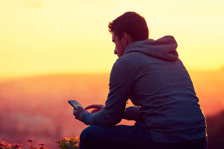 Young man with phone at the sunrise. Stock Photo - 45779084