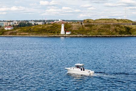 White lighthouse on bay near Halifax, Nova Scotia with white yacht Stock Photo - 41815562