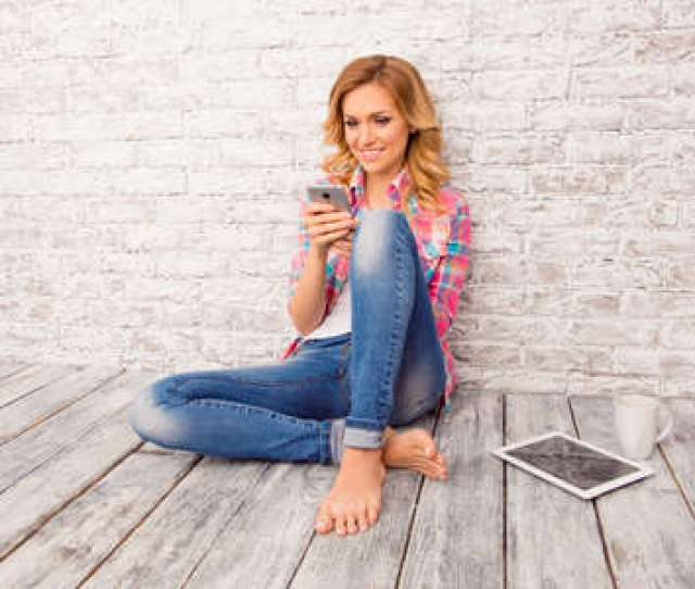 Happy Young Woman Sitting On Floor With Tablet Phone And Cup