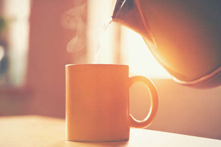 hot drinks: kettle pouring boiling water into a cup in morning sunlight Stock Photo