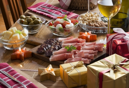 xmas food and drink: Full table of prosciutto, olives, cheese, salad and wine for holidays Stock Photo