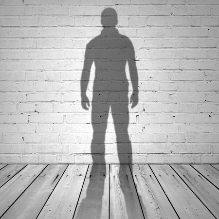 Shadow of a man on white brick wall and wooden floor Stock Photo - 31752604
