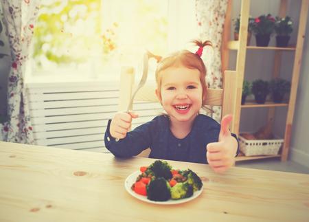 Bonne fille de l'enfant aime manger les légumes et les pouces montrant up Banque d'images - 51837569