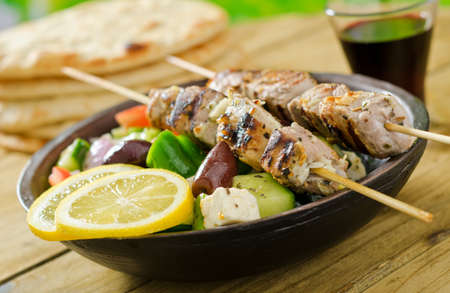 Grilled pork souvlaki skewers with greek salad and lemon. Stock Photo - 18935883