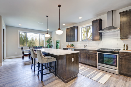 Modern Traditional American Kitchen Design In Grey Tones With         kitchen boasts dark wood cabinets  white backsplash subway tile and  over sized island with white and grey quartz counter illuminated by pendant  lights
