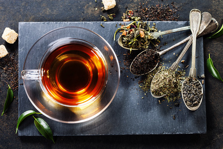 hot drinks: Tea composition with old spoon on dark background Stock Photo