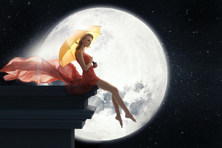 Lady with umbrella over full moon background Stock Photo - 27315639
