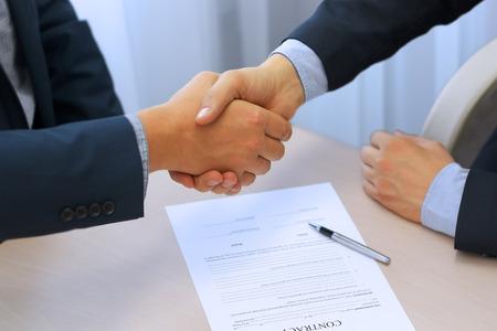 Primer plano imagen de un apretón de manos entre dos colegas después de firmar un contrato Foto de archivo - 46618811