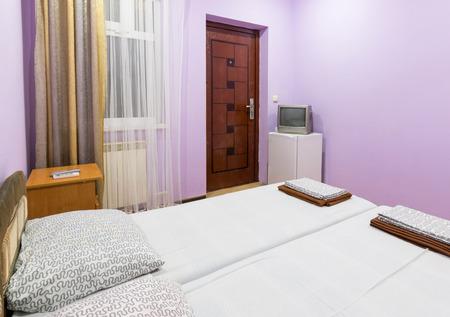 l interieur d une petite chambre avec un lit double une fenetre une television et un refrigerateur