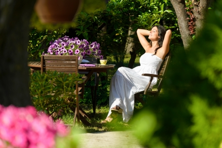 Happy woman resting in garden on summer sunny morning surrounded by flowers and trees. Young caucasian brunette relaxing and enjoying outdoors. Stock Photo - 20771915