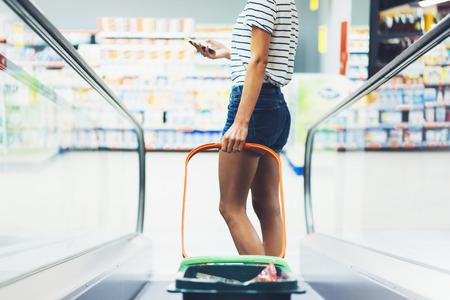 Jeune Femme En Short Jeans Avec Des Jambes Sexy, Faire Du Shopping Dans Le  Supermarché Flou Fond Orange. Mains Féminines Achètent Des Produits, En  Utilisant Un Téléphone Intelligent En Magasin. Personne De