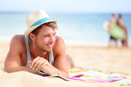 Man on beach lying in sand looking to side smiling happy wearing hipster summer hat. Young male model enjoying summer travel holiday by the ocean. Stock Photo - 20560160