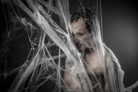 spider webs: Internet.man tangled in huge white spider web Stock Photo